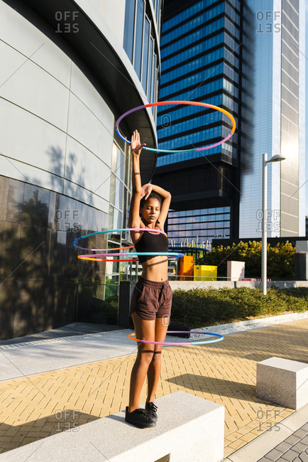 Young woman performing hula hoop dance with four rings in urban area