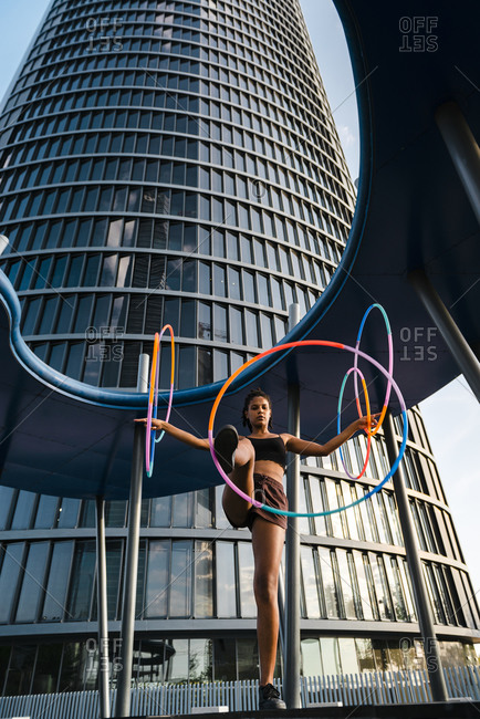 Generation z woman performing hula hoop dance with rings in downtown