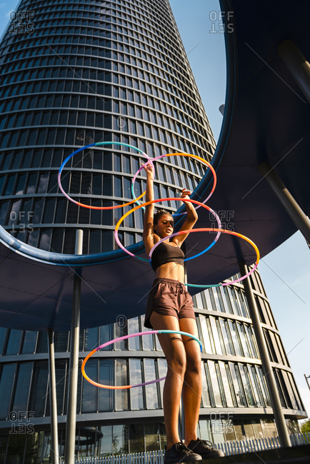 Active woman performing hula hoop dance with five rings in urban area