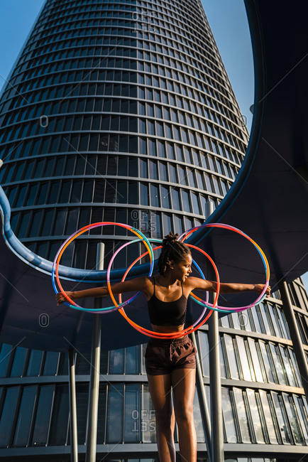 Generation z young woman holding five hula hoop in downtown at sunset