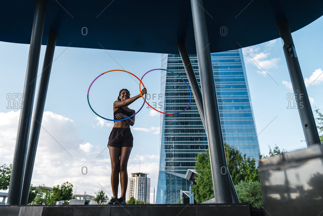 Active young woman holding five hula hoop in downtown at sunset