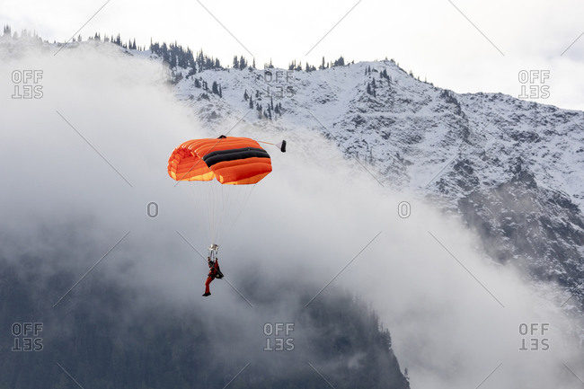 A paratrooper from the canada search and rescue fly in surrounded by mountains during a training mission.