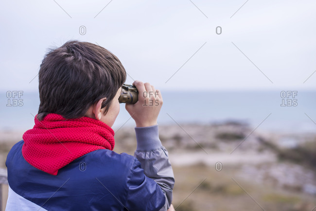 Playful boy looking through binoculars while standing on path