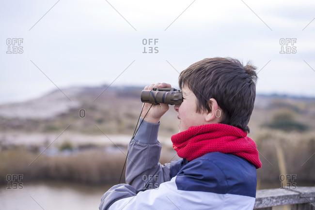 Playful boy looking through binoculars to the sea