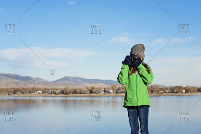 Young red hair girl with camera by a lake in the mountains