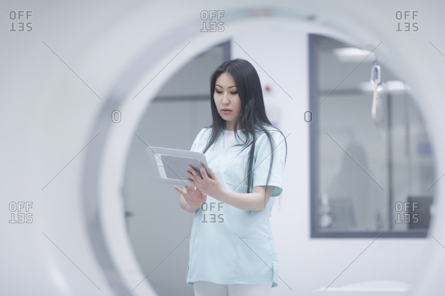 Asian woman nurse with tablet in a hospital