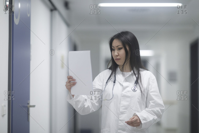 Asian woman doctor checking device in a hospital