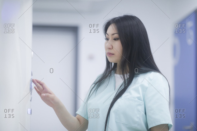 Asian woman nurse checking device in a hospital