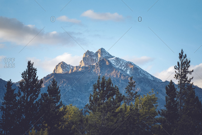 A mountain peak is illuminated by golden rays from the setting sun.