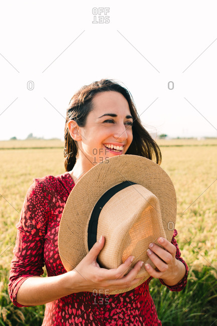 Portrait of happy brunette woman shaking her hair at sunset