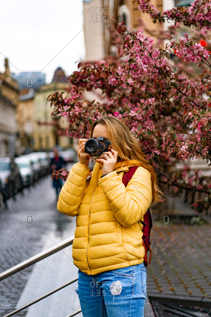 Young tourist woman taking pictures with a camera in old town europe