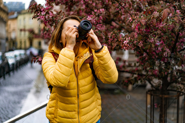 Young tourist woman taking pictures with a camera in old town europe.