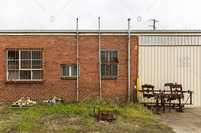 Old industrial brick building with grated windows and metal gate and abandoned rusty metal equipment placed nearby.