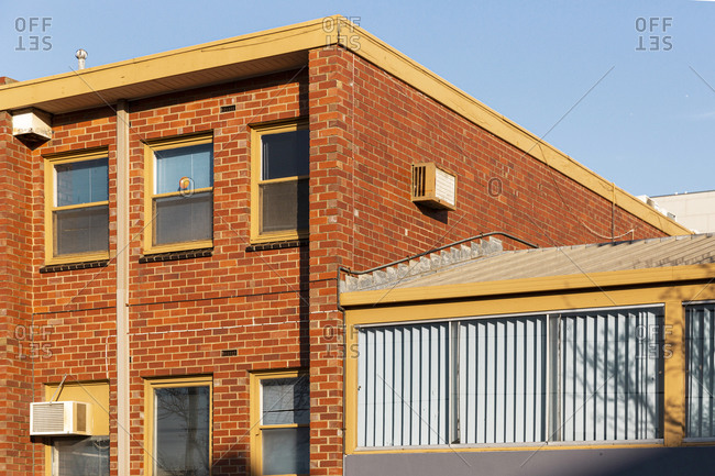 Modern low rise residential or office brick building and extension with wide windows against blue sky.