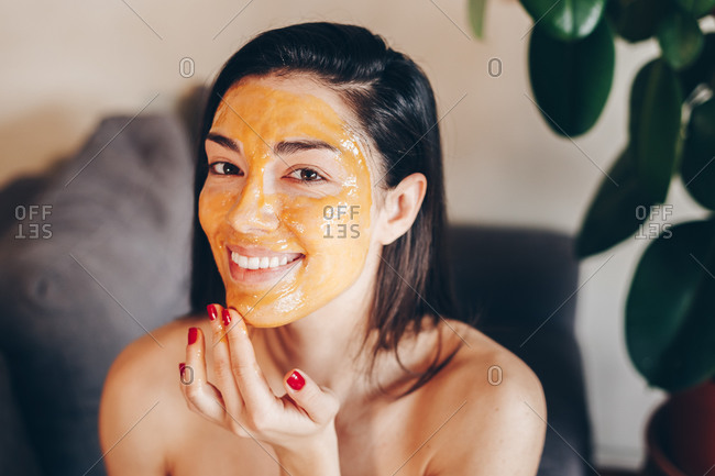Young beautiful Caucasian woman applying a natural honey peeling face mask at home. Smiling at the camera.