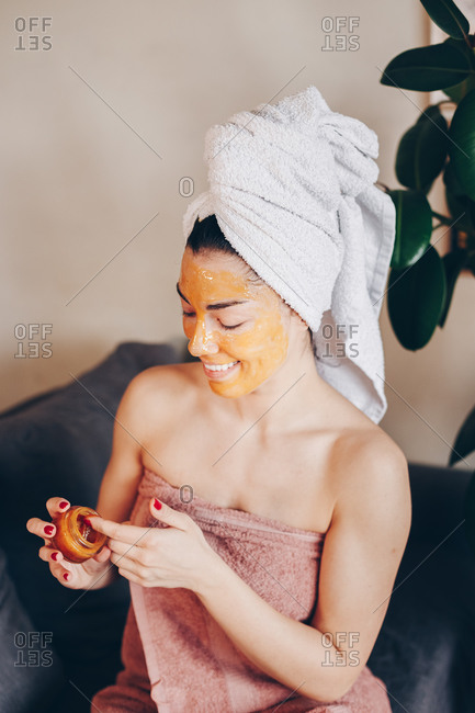 Portrait of beautiful young woman applying a natural honey peeling face mask at home. Skincare concept.