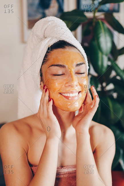 Young beautiful Caucasian woman applying a natural honey peeling face mask at home