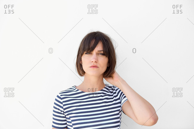 Portrait of young woman with striped shirt in front of a white wall