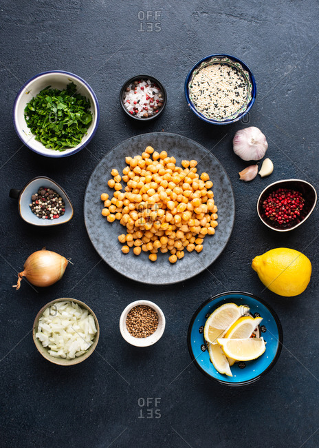 Ingredients for cooking falafel. Boiled chickpea on plate, sesame, garlic, lemon, onion, chopped greens, spices