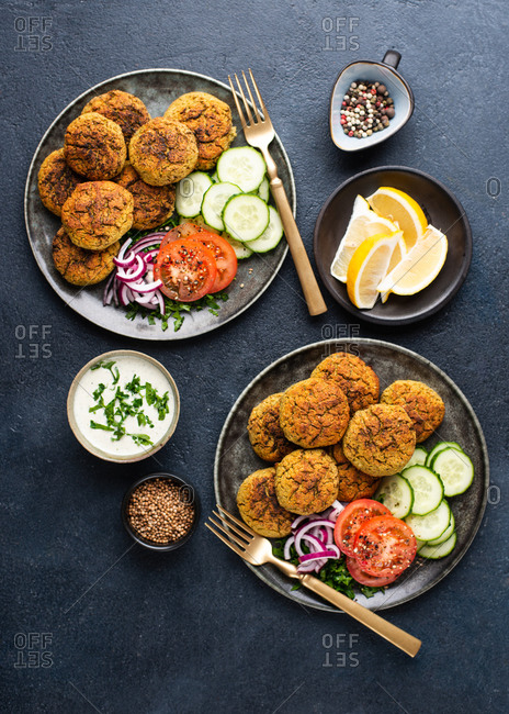 Two plates with falafel served with fresh vegetables on dark background