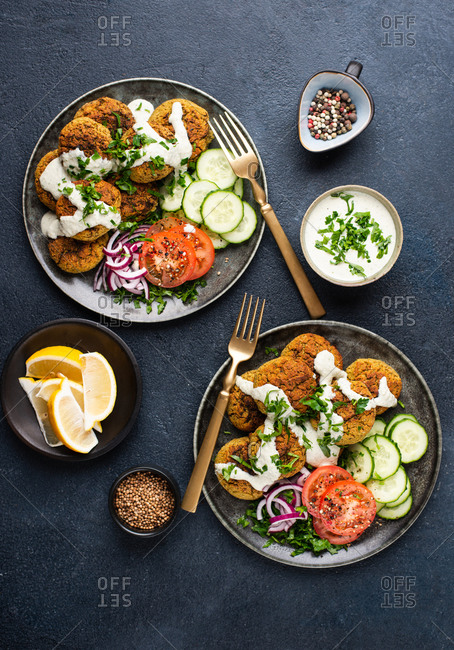 Two plates of falafel served with fresh vegetables and dip on dark background