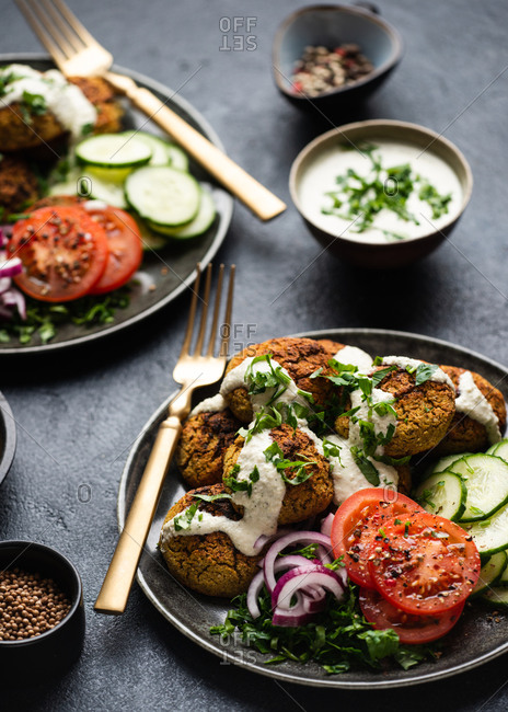 Two plates of falafel served with fresh vegetables and dip
