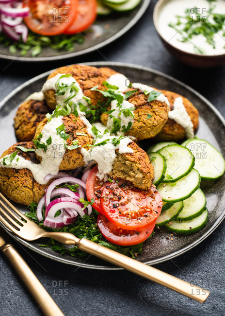 Plate of falafel served with fresh vegetables and dip