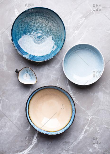 Set of empty blue ceramic bowls on gray background
