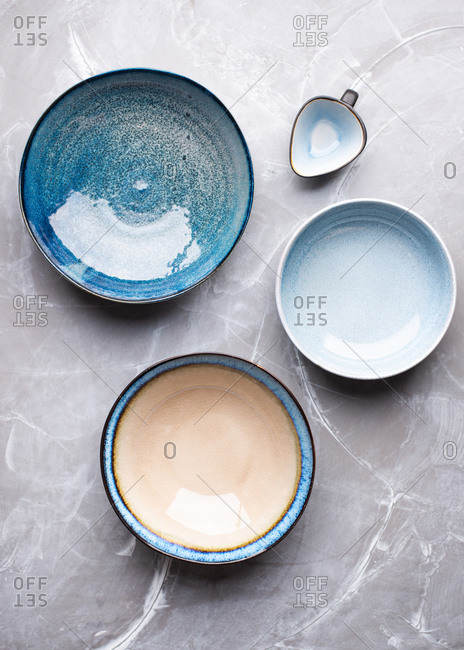 View from above of empty blue ceramic bowls on gray background