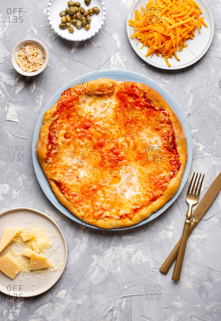 Overhead view of pizza with tomato sauce and cheese served on blue ceramic plate