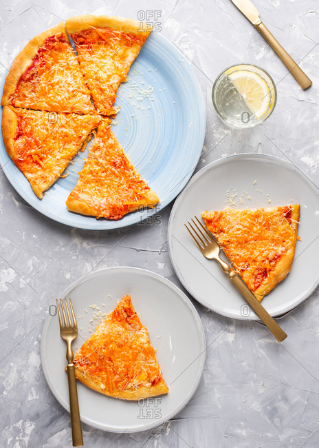Pizza with tomato sauce and cheese served on blue ceramic plate and glass of water