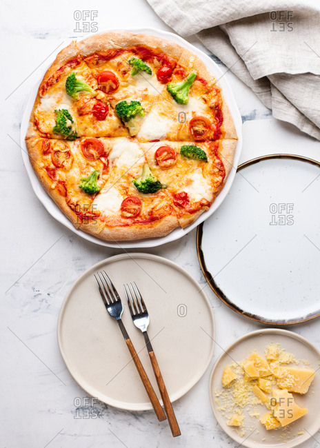 Overhead view of fresh sliced pizza with cheese mozzarella, broccoli and tomatoes