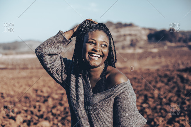 Woman touching her braids while standing in sunny rural setting