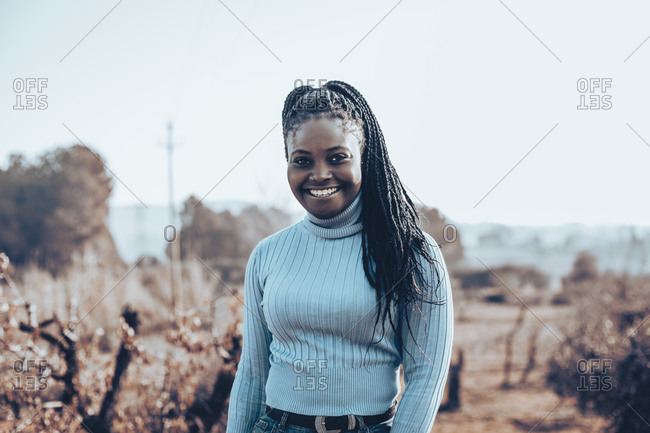 Woman with braids wearing a blue turtleneck sweater in a rural setting