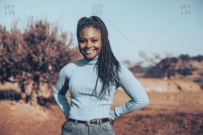 Woman with braids wearing a blue turtleneck sweater standing in a rural setting