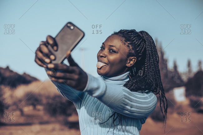 Young woman with braids sticking her tongue out while taking selfies in a rural setting