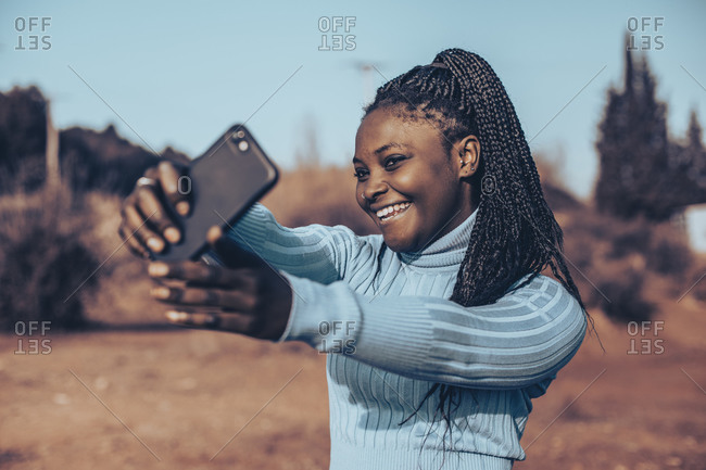 Beautiful young woman with braids smiling and taking selfies in a rural setting