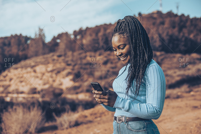Side view of beautiful young woman with braids using cell phone in a rural setting