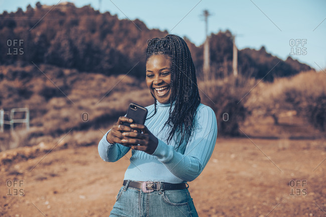 Young woman with braids smiling using cell phone in a rural setting