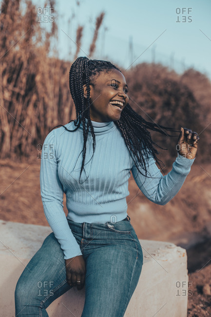 Woman with braids wearing a blue turtleneck sweater sitting in a rural setting laughing and looking away