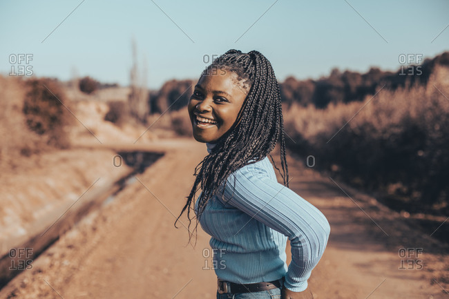 Beautiful woman with braids smiling and looking at camera on a dirt road