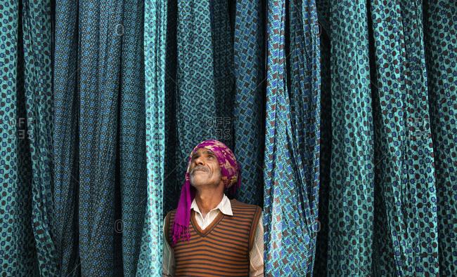 Jaipur, India - January 2, 2020: Textile worker inspecting hanging, freshly dyed cloth, Jaipur, India