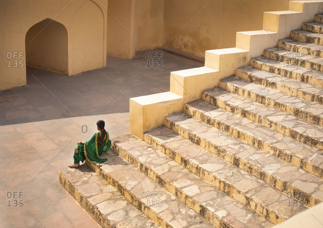 Indian woman resting on steps at the Jantar Mantar Astrological Park, Jaipur, India
