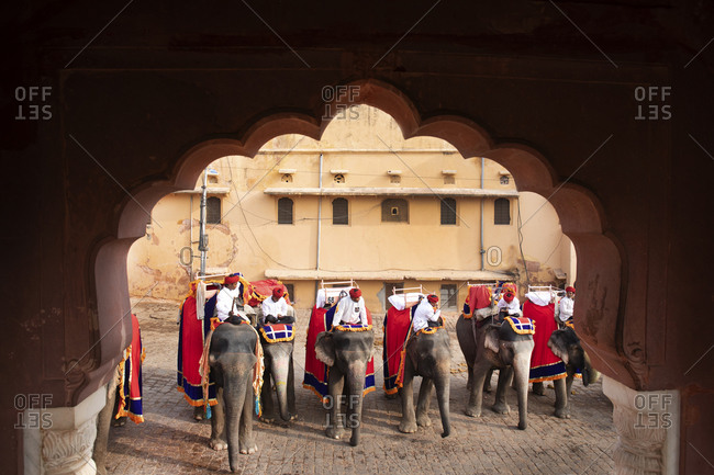 Jaipur, India - January 4, 2020: View through arch of tour guides on elephants visiting Amber Fort, Jaipur, India