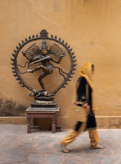 Indian woman walking by a shop/tourist store display of Vishnu Hindu God, Amber Fort Palace complex, Jaipur, India