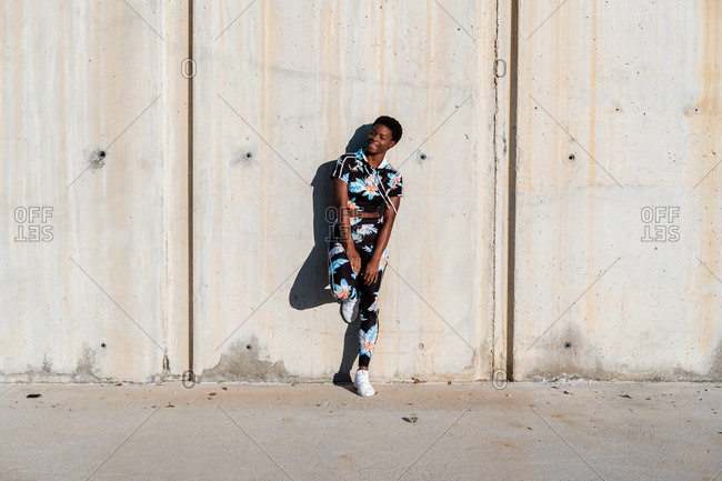 Cheerful confident African American female athlete in flowered sport clothes and white sneakers looking away with interest and laughing while standing alone leaning on concrete wall in sunbeams and resting after training in city