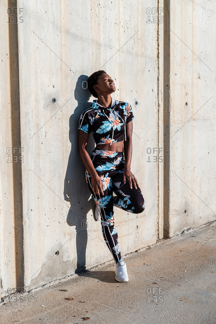 Cheerful confident African American female athlete in flowered sport clothes and white sneakers with closed eyes with interest and laughing while standing alone leaning on concrete wall in sunbeams and resting after training in city