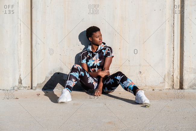African American female athlete in flowered sport clothes and white sneakers looking away while sitting alone on concrete wall in sunbeams and resting after training in city