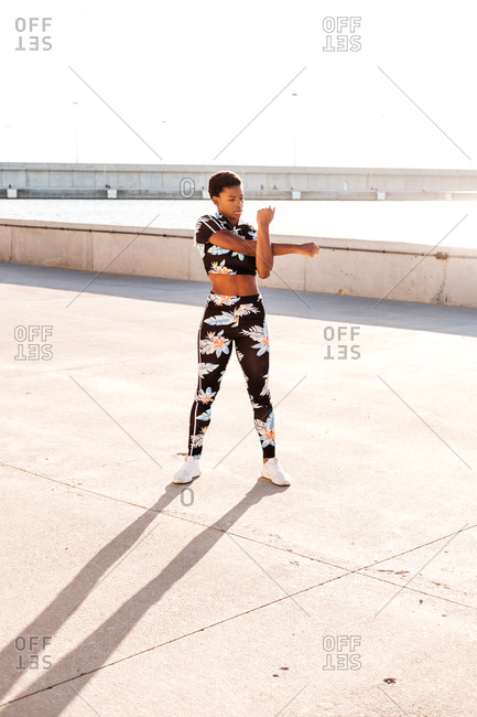 Focused African American adult woman in flowered sportswear stretching hand muscles while standing alone and warming up before training among urban environment in sunny day