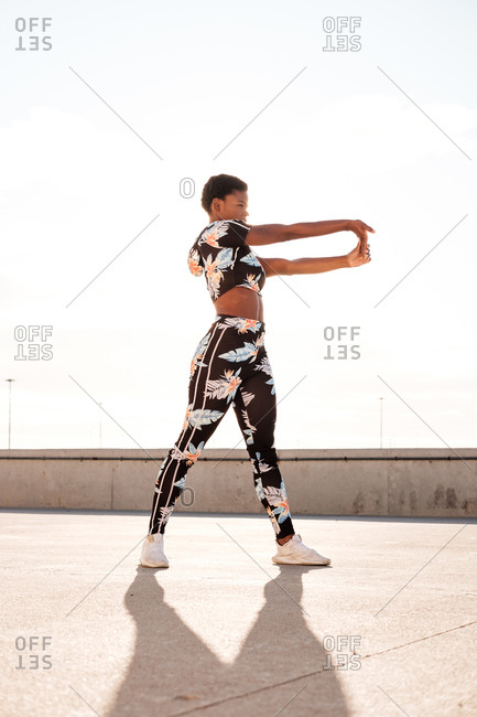 From below focused African American adult woman in flowered sportswear stretching hand muscles while standing alone and warming up before training among urban environment in sunny day